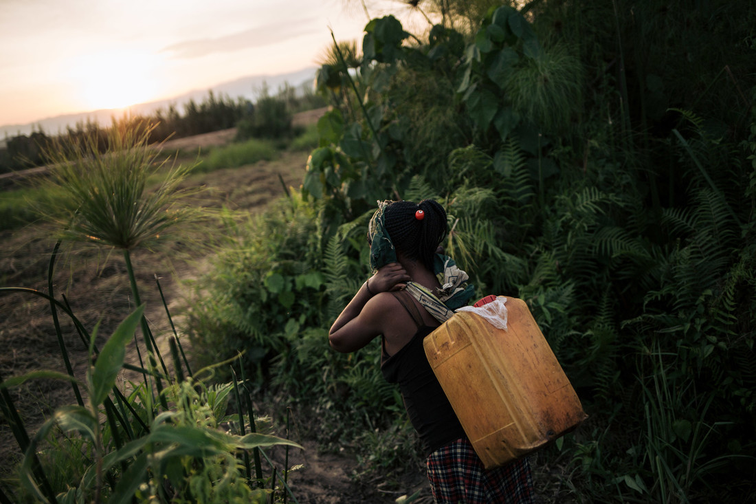 A woman carries water water on the outskirts of Malende